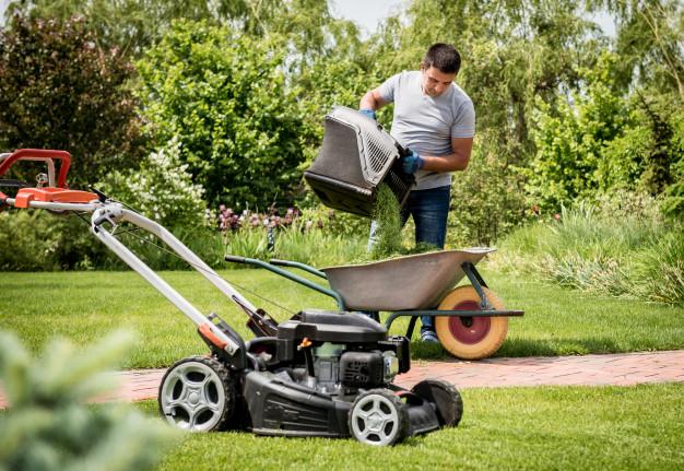 jardinero-vaciando-cortacesped-carretilla-despues-cortar-cesped_179755-9060